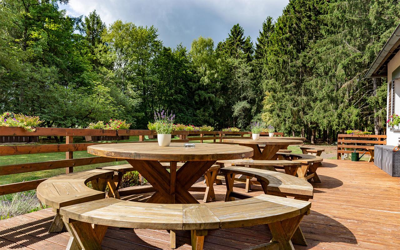 Grosse-Terrasse-im-Waldhotel-am-Nuerburgring-in-der-Eifel-in-Baar-mit-grosser-Wiese-und-Wald